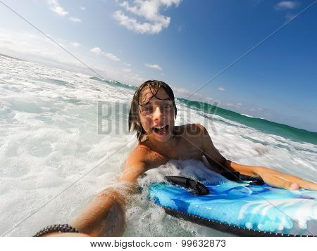 Caucasian male boy enjoys riding the waves with a surfboard. Summer sunny day.