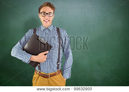 Geeky businessman holding a clipboard against green chalkboard
