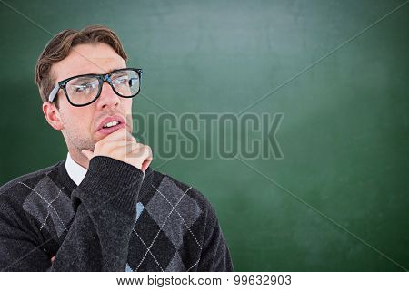Geeky hipster thinking with hand on chin against green chalkboard
