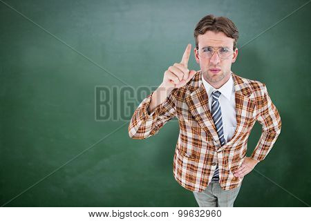 Upset geeky hipster pointing at camera against green chalkboard