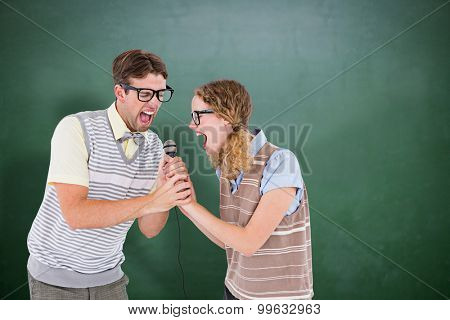 Geeky hipster couple singing into a microphone against green chalkboard