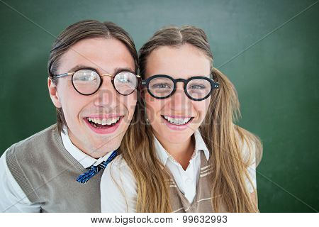 Geeky hipsters smiling at camera against green chalkboard