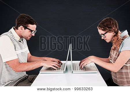 Geeky hipster couple using laptop against blackboard
