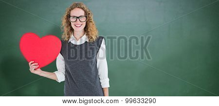 Geeky hipster holding heart card against green chalkboard