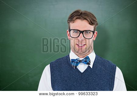 Geeky hipster looking at camera against green chalkboard