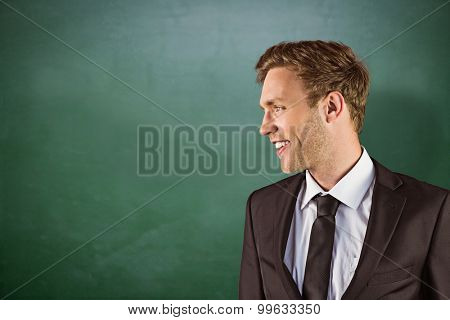 Young handsome businessman looking away against green chalkboard