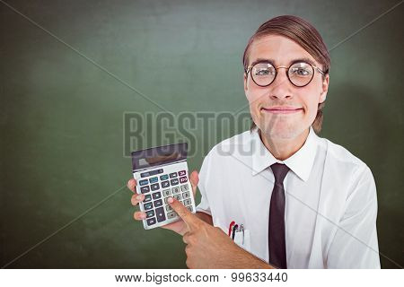 Geeky smiling businessman showing calculator against green chalkboard