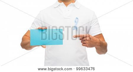 medicine, health care, gesture and people concept - close up of middle aged latin man in t-shirt with sky blue prostate cancer awareness ribbon holding blank paper card