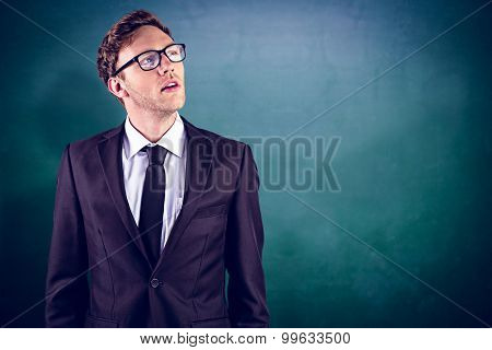 Young businessman thinking and looking up against green chalkboard