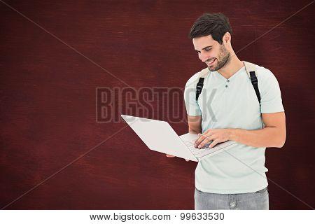 Student using laptop against desk