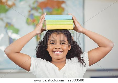 Portrait of smiling pupil balancing books on head in a classroom in school