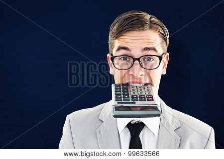 Geeky smiling businessman biting calculator against navy blue