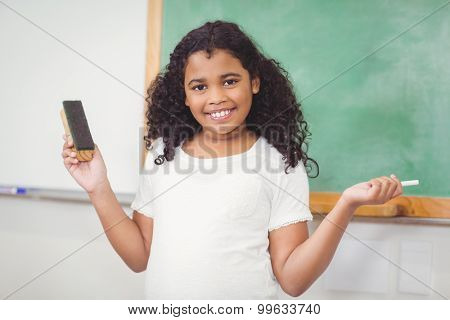 Portrait of smiling pupil holding chalk in a classroom in school