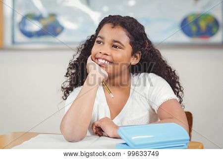 Cute pupil daydreaming in a classroom in school