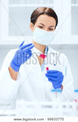 science, chemistry, biology, medicine and people concept - close up of young female scientist with test tube and pipette making research in clinical laboratory