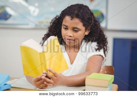 Concentrated pupil reading book in a classroom in school