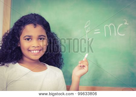 Portrait of smiling pupil standing in front of chalkboard in a classroom