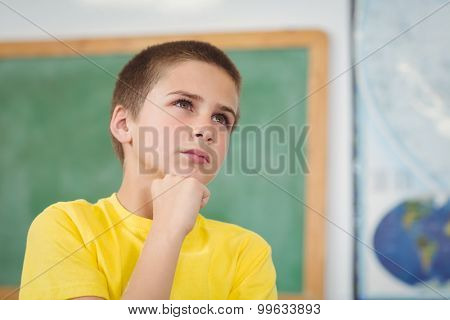 Concentrated pupil having hand on chin in a classroom in school
