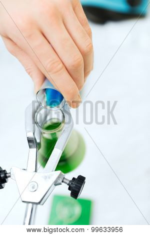 science, chemistry, biology, medicine and people concept - close up of scientist hand filling test tubes and making research in clinical laboratory