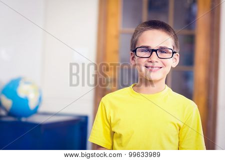 Portrait of smiling pupil wearing glasses in a classroom in school