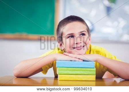 Smiling pupil leaning on pile of books in a classroom in school