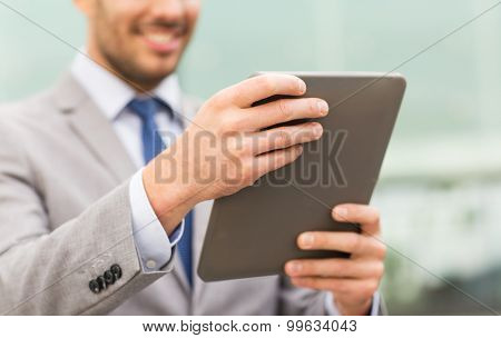 business, technology and people concept - close up of smiling man with tablet pc computer in city