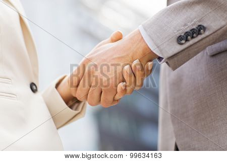 business, partnership, success, gesture and people concept - close up of business couple shaking hands on city street over office building