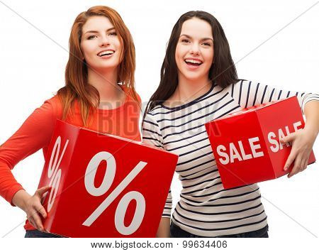 shopping, sale, and gift sconcept - two smiling teenage girls with percent and sale sign on red box