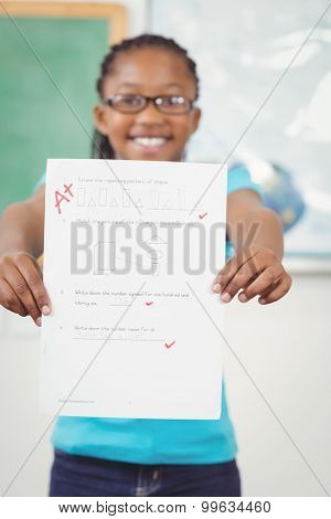 Portrait of proud pupil showing test result to camera in a classroom
