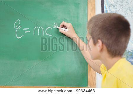 Cute pupil writing on chalkboard in a classroom in school