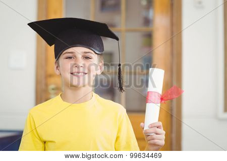 Portrait of smiling pupil with mortar board and diploma in a classroom
