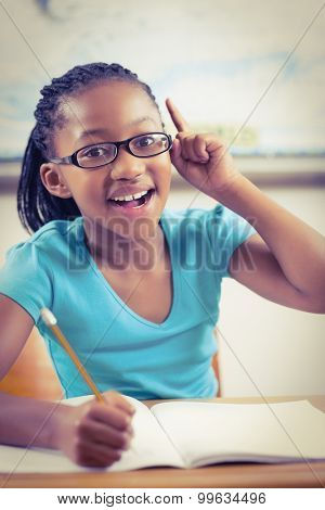 Portrait of cute pupil having an idea in a classroom in school
