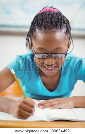 Smiling pupil working at her desk in a classroom in school