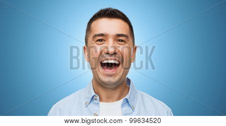 happiness, emotions and people concept - laughing man over blue background