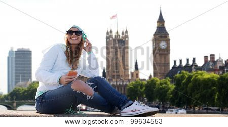 technology, travel, tourism, vacation and people concept - smiling young woman or teenage girl with smartphone and headphones listening to music over london city background