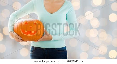 holidays, halloween, decoration and people concept - close up of woman with carved pumpkin