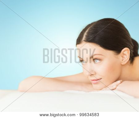 people, beauty and body care concept - happy beautiful woman lying on massage desk at spa over blue background