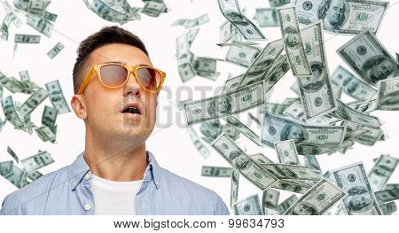 business, finance, luck, fortune and people concept - face of scared or surprised middle aged latin man in sunglasses with heap of falling dollar money