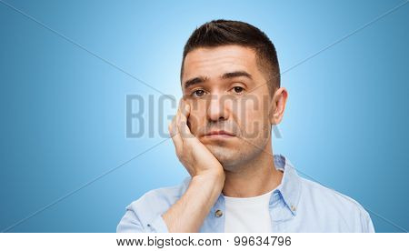 emotions and people concept - bored middle aged man face over blue background