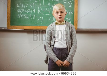 Portrait of pupil dressed up as teacher in front of chalkboard in a classroom