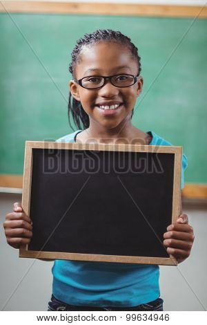 Portrait of smiling pupil holding chalkboard in a classroom in school