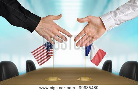 United States and France diplomats agreeing on a deal