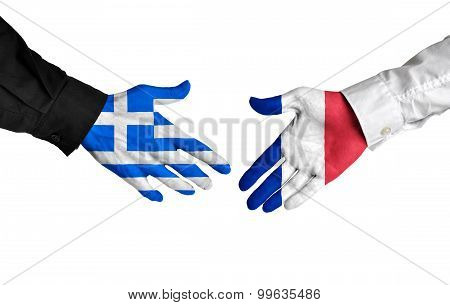 Greece and France leaders shaking hands on a deal agreement