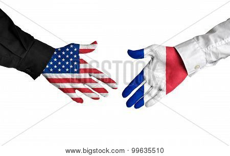 United States and France leaders shaking hands on a deal agreement
