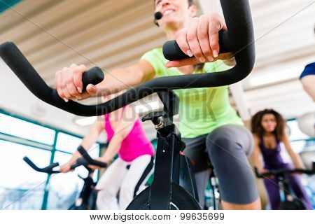 Woman at Fitness Spinning on bike in gym, shot from a low angle