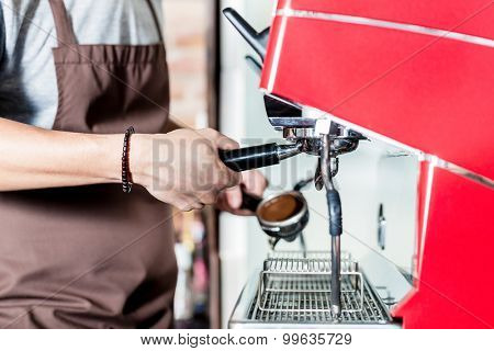 Barista preparing coffee on portafilter machine in cafe, macro on hands