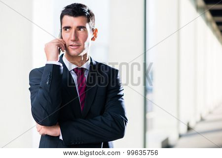 Business man with phone outdoors standing in front of building