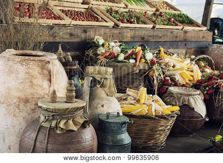 Mix Of Vegetables In Wooden Containers And Wicker Baskets With Clay Pots And Metal Milk Container In