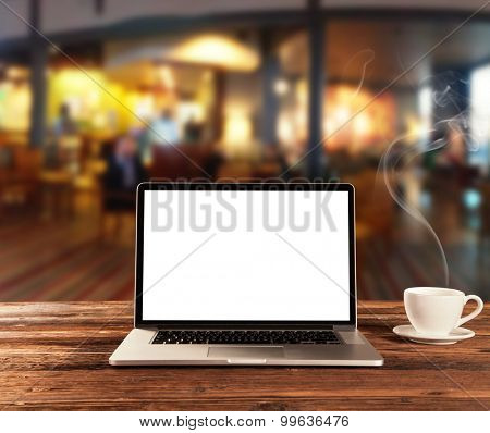 Laptop with blank screen placed on wooden table in coffee shop