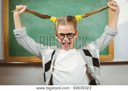 Portrait of cute pupil pulling her hair in a classroom in school